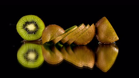 exotic dishes : Fresh cutted kiwi falling between two other kiwies cut in a half. Kiwies are placed on the wet reflective surface.