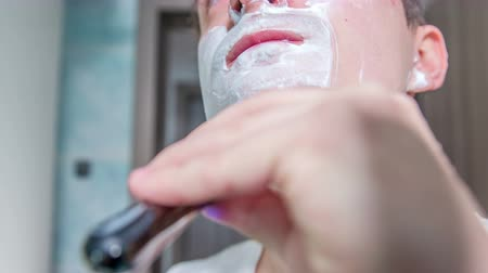 shaving foam : A young man has already shaven half of his beard. There is still a lot of foam on his face.