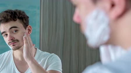 shaving foam : A young man is putting shaving foam on the left and right cheek and then on his chin. Stock Footage