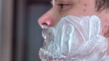 shaving foam : A young man is puttig foam on his face with his fingers.
