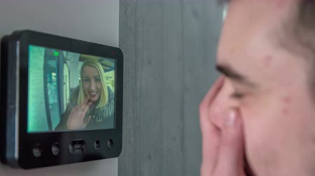 shaving foam : A young woman is standing in front of the door outside the house and her boyfriends sees her on the screen. This is the camera that monitors who is standing outside the house. A young woman is showing the guy to check his time. Stock Footage