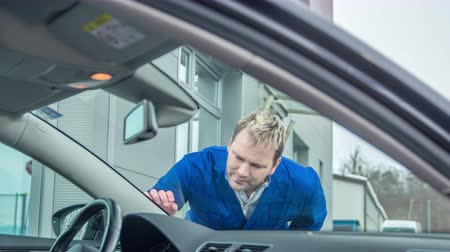 yedek : A young man touches the crack on the front window of the car and he is annoyed about it.