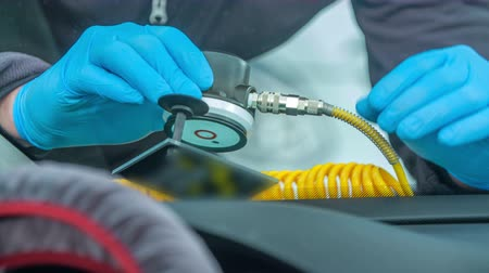 shattered : A young man is checking the crack on the front window of the car. He is wearing special blue gloves. Stock Footage