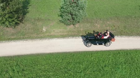 bastião : A young couple that just got married is driving in a vintage car. Aerial shot. A driver is driving a car and theyre sitting in the back. Its a nice and warm day. Stock Footage