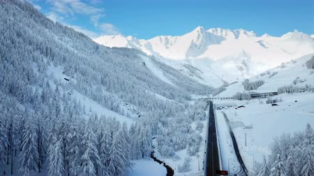 faház : Alps in Switzerland are covered with snow. Its winter time. The scenery is breathtaking. Only the road is clean.