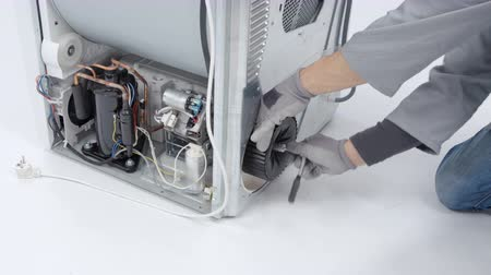 caja de herramientas : A repairman is fixing a drain pump filter on a washing machine. He needs to find out where the problem is. Archivo de Video