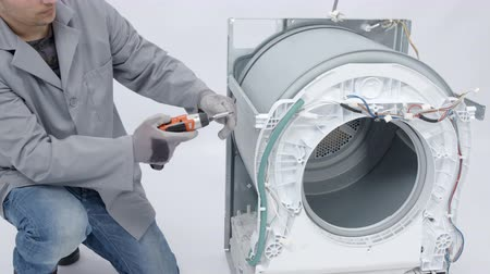 ремонтировать : A man is dismantling a whole washing machine and he is trying to fix it.