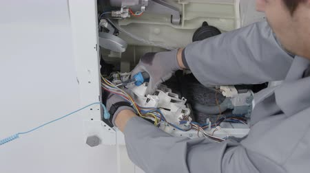 toolbox : A man is working hard and he is trying to fix a problem on a washing machine. Stock Footage
