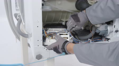 toolbox : A man is trying to find a problem and fix a washing machine. He is using safety gloves. Stock Footage