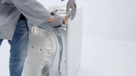 toolbox : A man is taking out screws from a washing machine and he is using a drill. Stock Footage