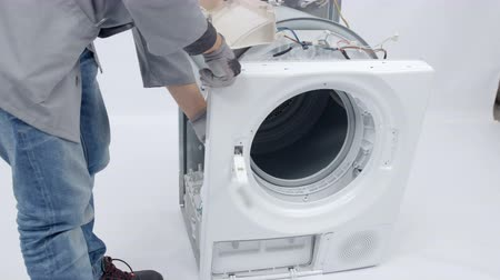 toolbox : A repairman is fixing the front side of the washing machine. He needs to dismantle the whole device to be able to solve the problem.