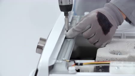 lavanderia : A man is taking out a couple of screws from the side of the washing machine. He is using a drill for that. He is wearing safety gloves. Stock Footage