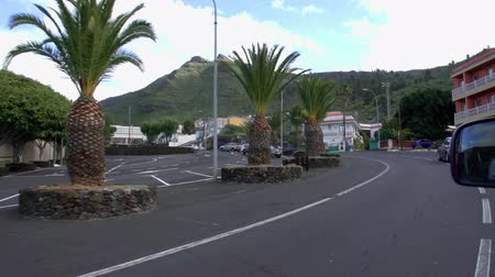 substituição : A car is driving on the road in a town. There are palm trees on the side of the road. Vídeos
