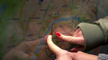 dönt : Two people are putting their fingers on a map and they decide where they want to go.