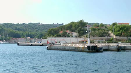 rekreasyon : We can see a harbour and a small sea town. The sun is shining and it looks like its going to be a beautiful summer day. Stok Video