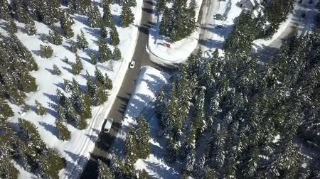 レクリエーション : Two vehicles are driving one after the other in a village at a skiing resort. Aerial shot.