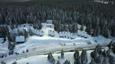 отдыха : There are plenty of wooden houses at a skiing resort. All the roofs are covered with snow. Aerial shot. Стоковые видеозаписи
