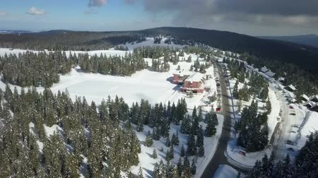 отдыха : We can see a nice village in a skiing resort. Aerial shot. There are many forests with spruce trees there, too.