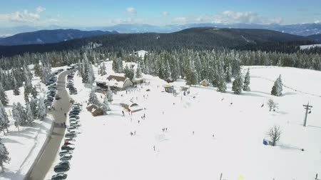 śnieżka : Its a gorgeous sunny day at a ski resort. People are skiing and are enjoying themselves.