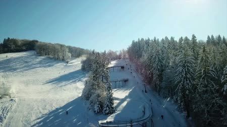 есть : There is a lot of snow at Celjska koca resort. Aerial shot. Its a nice winter day and lots of people are spending their time outdoors. Стоковые видеозаписи