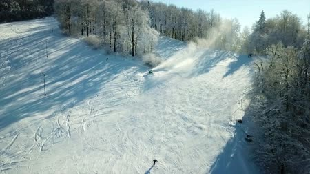 еще : Children are skiing downhill one by one. The hill is pretty steep. Its a sunny yet cold day.