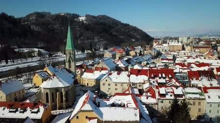 může : We can see the old town of Celje in winter time The roofs of the houses are covered with snow. Its a cold day.