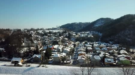 еще : A part of town lying next to a hill. Its winter time. Aerial shot. The day is clear yet cold.