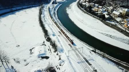 margem do rio : A train is riding on rails and is heading towards the railway station in a town of Celje. Its winter time. Aerial shot.