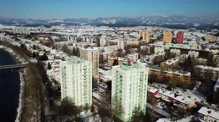 margem do rio : There are a few skyscrapers in a town of Slovenia. Its winter time. Aerial shot.