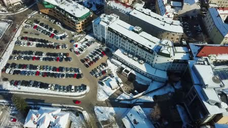 nyaraló : Its winter time in the town of Celje. There is snow around parking lots, schools, hospitals and apartments. Aerial shot. Stock mozgókép
