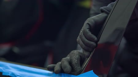 shattered : A mechanic is fixing a car window in an automobile repair shop. He is wearing safety gloves. Stock Footage