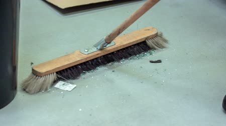 yedek : A man is sweeping the floor with a large broom because there has been some glass broken. This is taking place in a car repair shop.