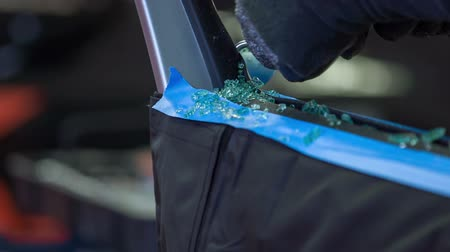 shattered : A mechanic is cleaning the car door because there has been broken glass everywhere. Stock Footage