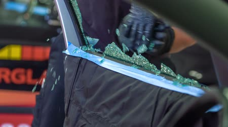 o : A mechanic is about to start fixing a broken car window. He holds the broken pieces of the glass and throws them on the ground in a car repair shop. He is wearing safety gloves. Stok Video
