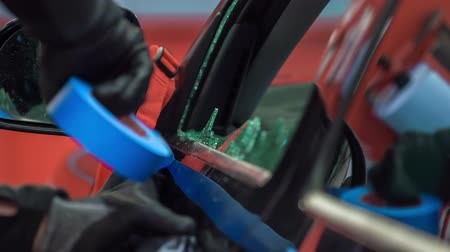 süpürge : A mechanic is putting a blue tape under a car window on the car. He is about to fix a broken car glass in the automobile repair shop.