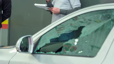 shattered : A man is standing by the car which has a broken drivers window and he is writing down notes about something.