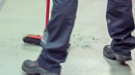 ремонт : A young mechanic is sweeping the floor in the car repair shop. A front car window was broken. Стоковые видеозаписи