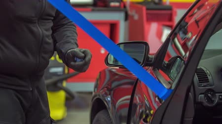 substituição : After a car has been fixed and a broken front window replaces, a mechanic is taking down a blue tape that was on the front door of a vehicle. Stock Footage