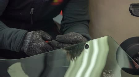 shattered : A mechanic is fixing a front window of the car in an automobile repair shop. He is wearing safety gloves.