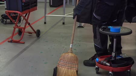 üveges : A mechanic is sweeping the floor after the work has been finished. There is some broken glass on the ground. Stock mozgókép