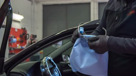 üveges : A mechanic is fixing his safety glasses before starting to repair a car.