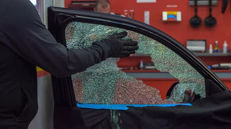üveges : A man is carefully holding pieces of a broken window and is then letting them fall on the ground in a car repair shop. Stock mozgókép