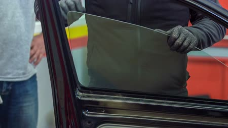 üveges : A mechanic is trying to put in a new car window. A previous car window was broken.