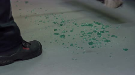 üveges : A glass has been broke and someone is slowly sweeping the floor to clean it up.