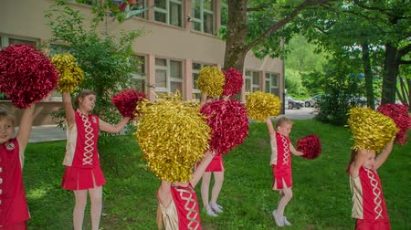bastoni : Holding their yellow and red pom-poms and practising the choreo for their performance. Filmati Stock