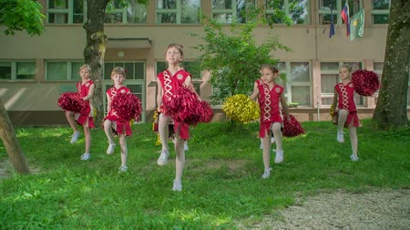 pom : Primary school girls are practising their routines for the school performance. Theyre dancing in the school yard.