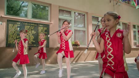 vara : Girls are wearing red costumes and are practising with their majorette sticks. This is taking place in the school yard. Vídeos