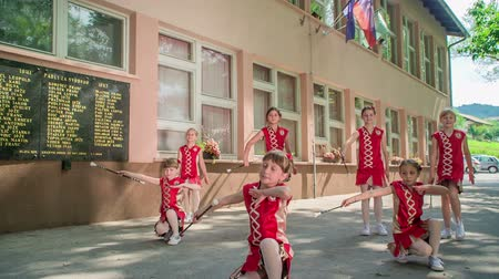 pom : Small girls are practising the routine with their majorette sticks. Theyre dancing outside. Stock Footage
