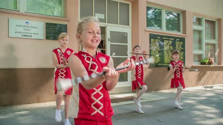 pom : Happy girls are practising their dancing outside of school. Theyre holding the majorette sticks.