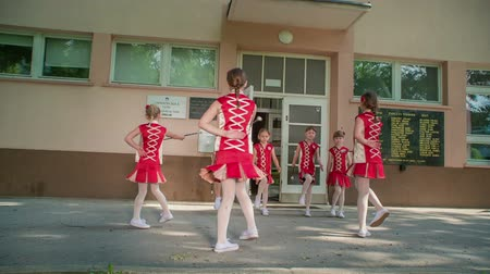 pom : A group of girls is practising dancing with majorette sticks. They look happy and are smiling.